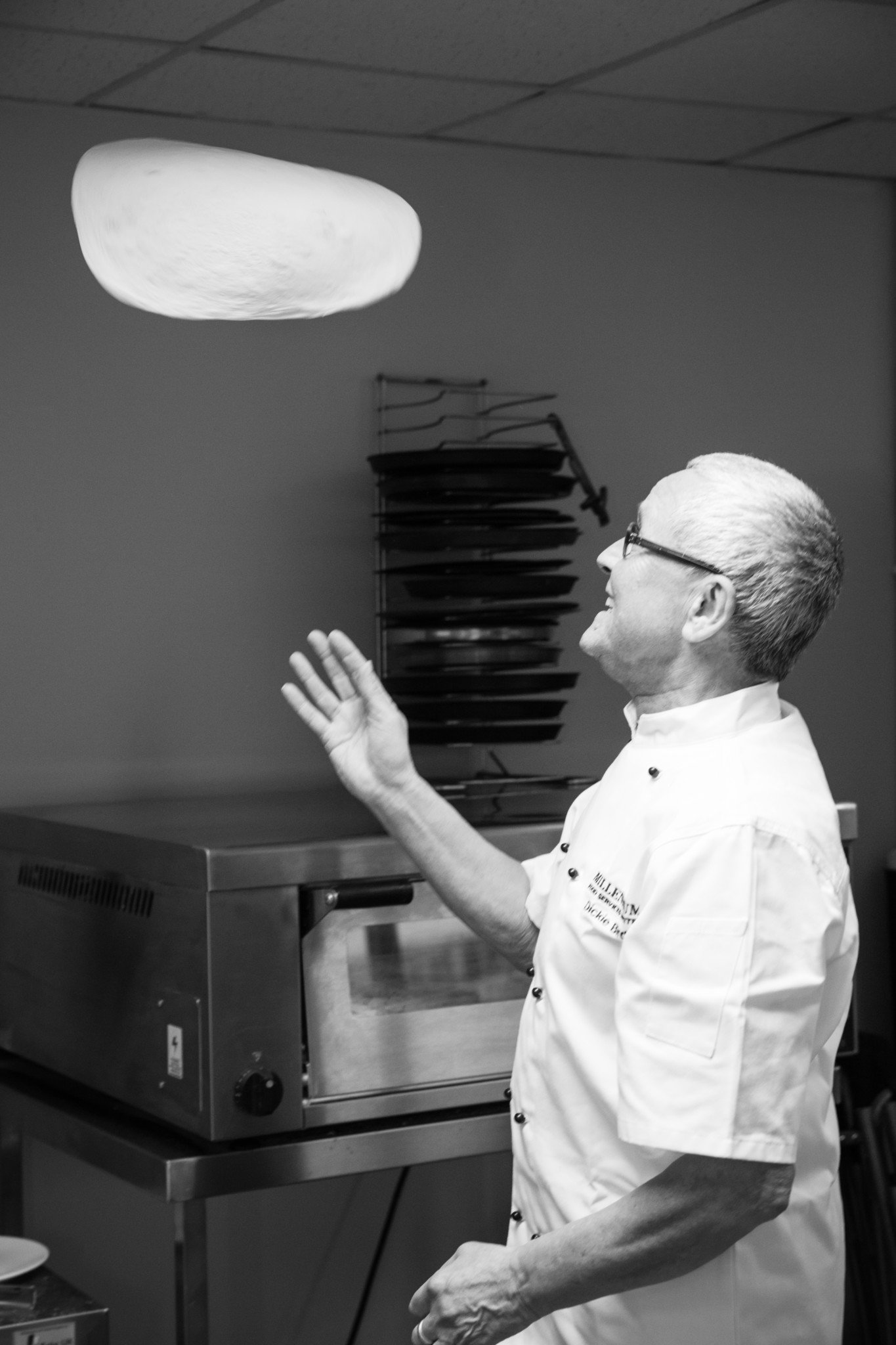 Chef hand throwing pizza dough