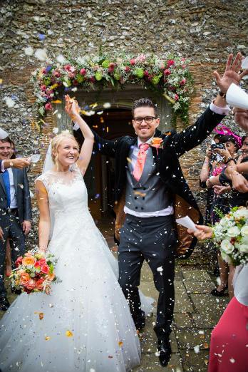 Wedding Couple raise their arms in celebration