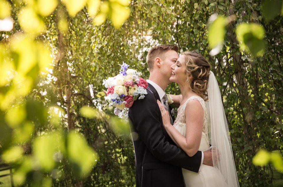 Bride & Groom kissing under trees