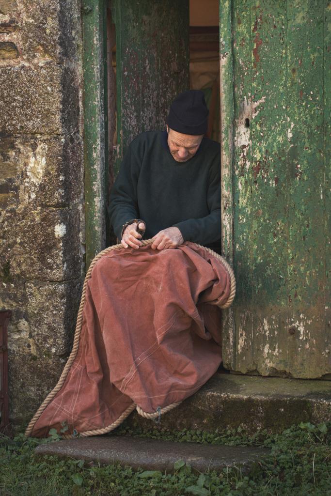 sailmaker sat on steps sewing